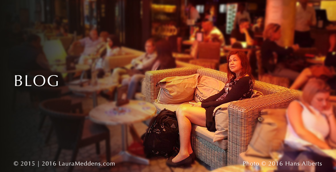 BLOG Page Banner photo shows Laura Meddens sitting at an outdoor patio of a restaurant in Amsterdam while overhead heaters cast an orange glow on everyone on a rainy day.