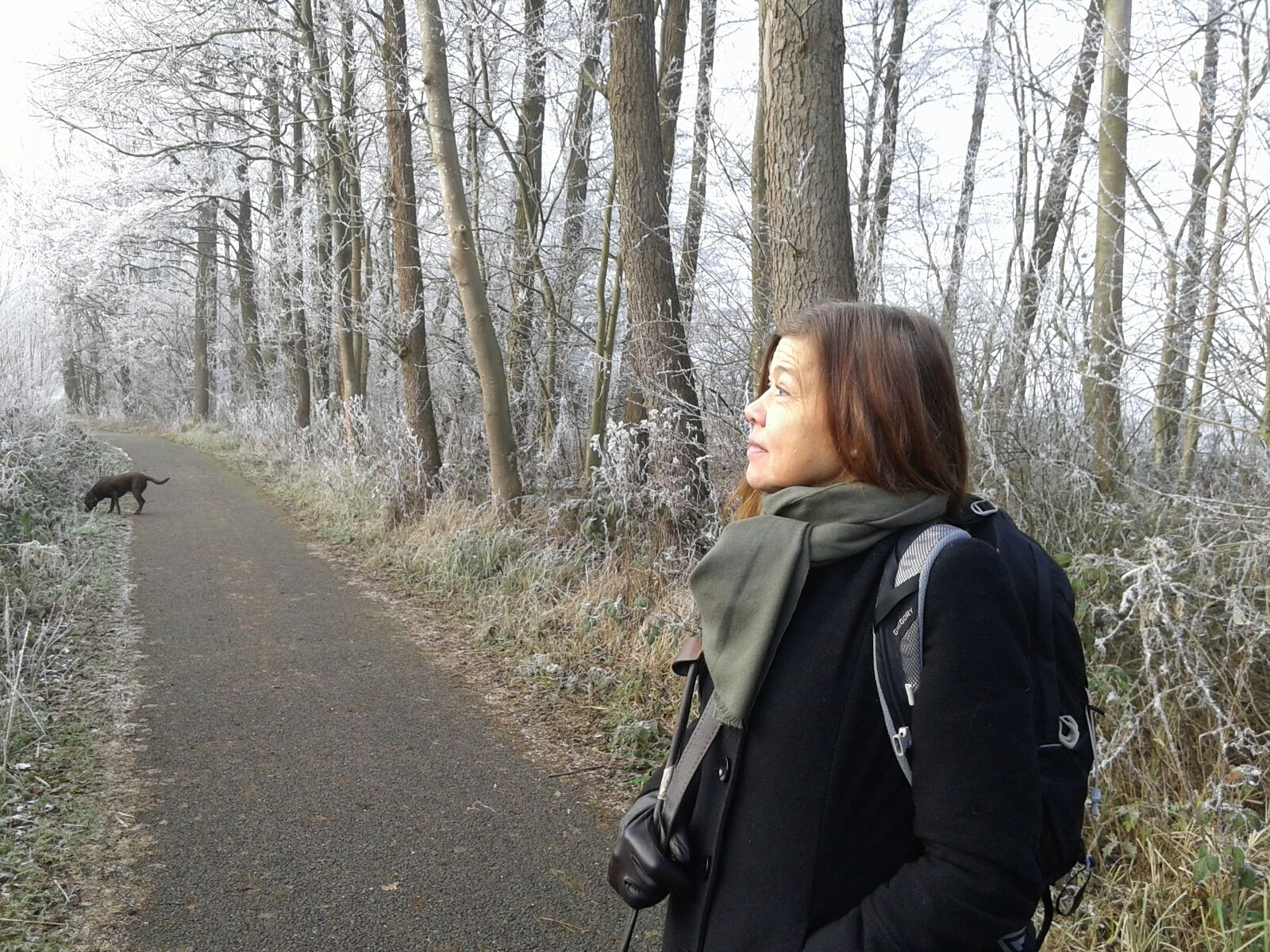 Laura Meddens stands with her guide dog Nugget along the shore with some frosted trees behind her in Amsterdam.