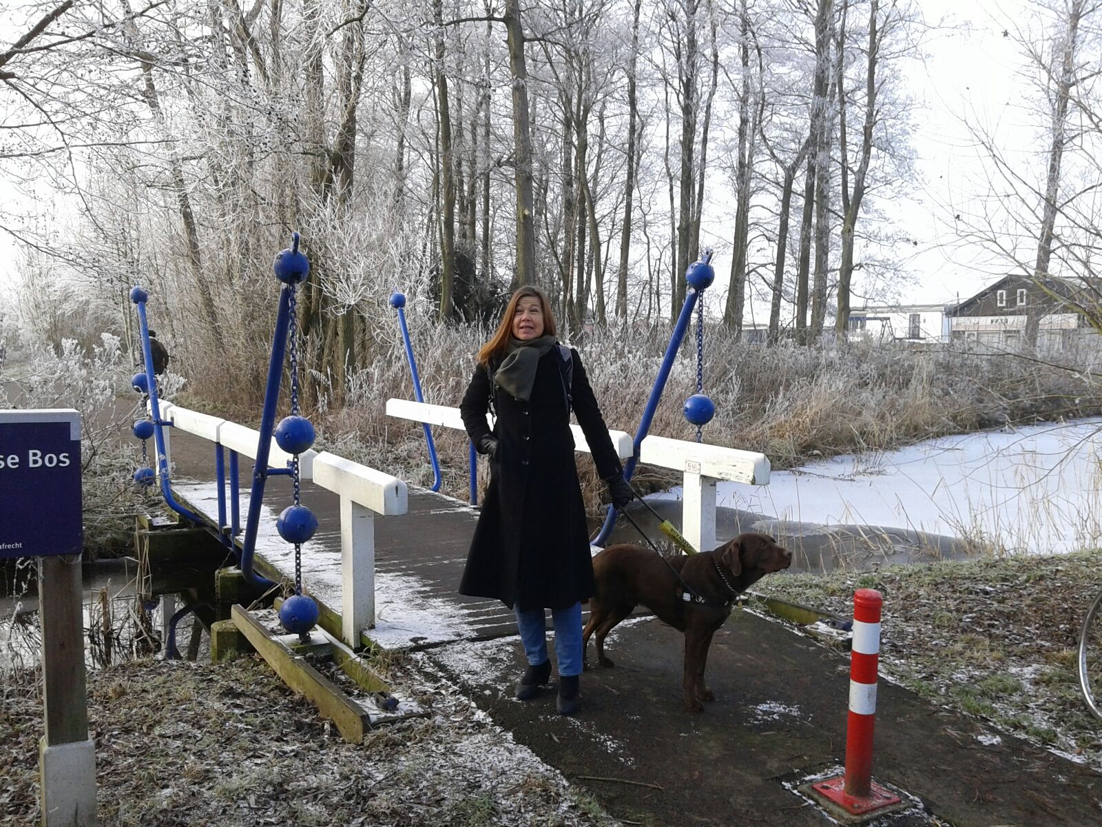 Laura Meddens stands with her guide dog Nugget along the shore with some frosted trees and a footbridge over a canal behind her in Amsterdam.