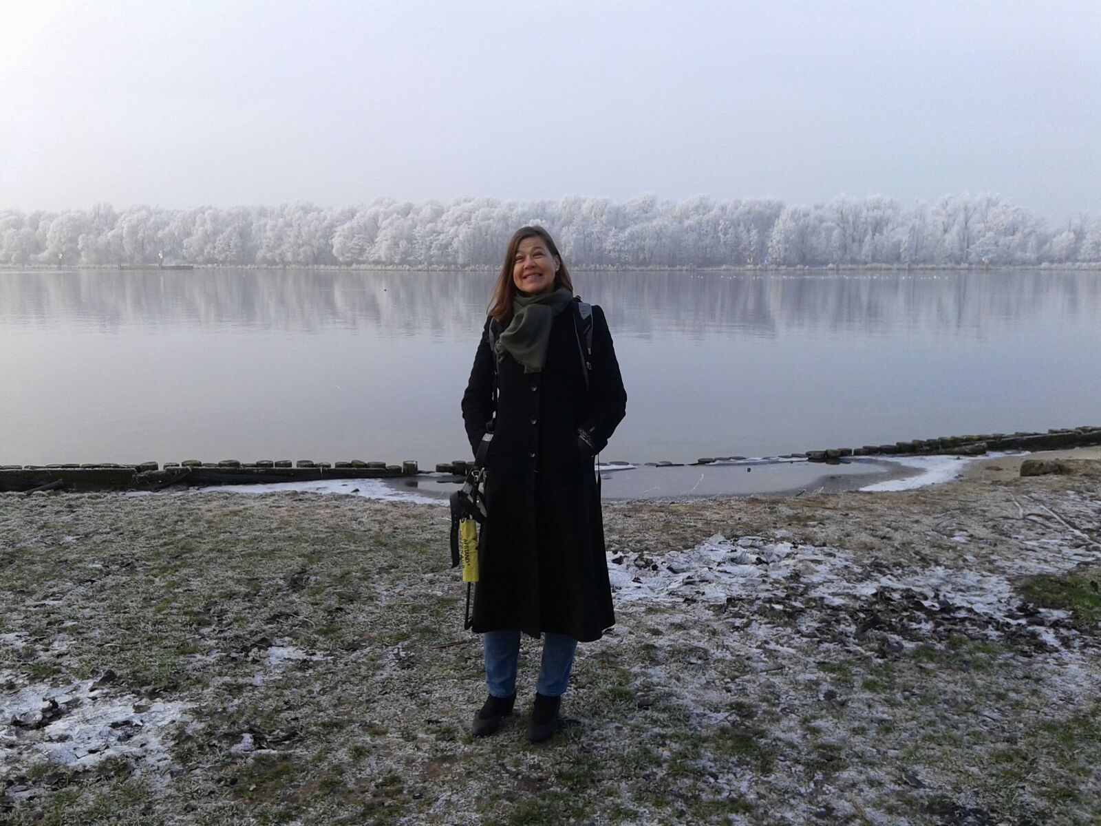 Laura Meddens stands near the shore in Amsterdam with a line of frosted trees on the horizon.