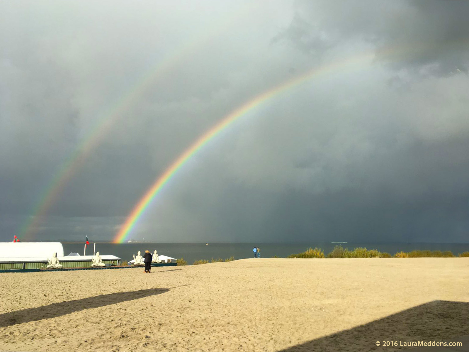 photo shows two parallel rainbows in the sky over Blijburg Beach in Ijburg, with t