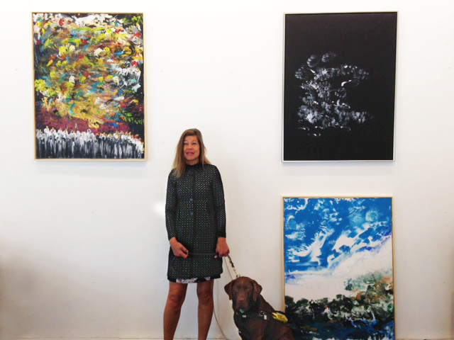 Photo shows Laura Meddens and her Seeing Eye® guide dog Nugget at Open Ateliers Oost with her paintings (clockwise from left) 'Chorus of Love', 'Tango', and 'Celestial Avalance'.
