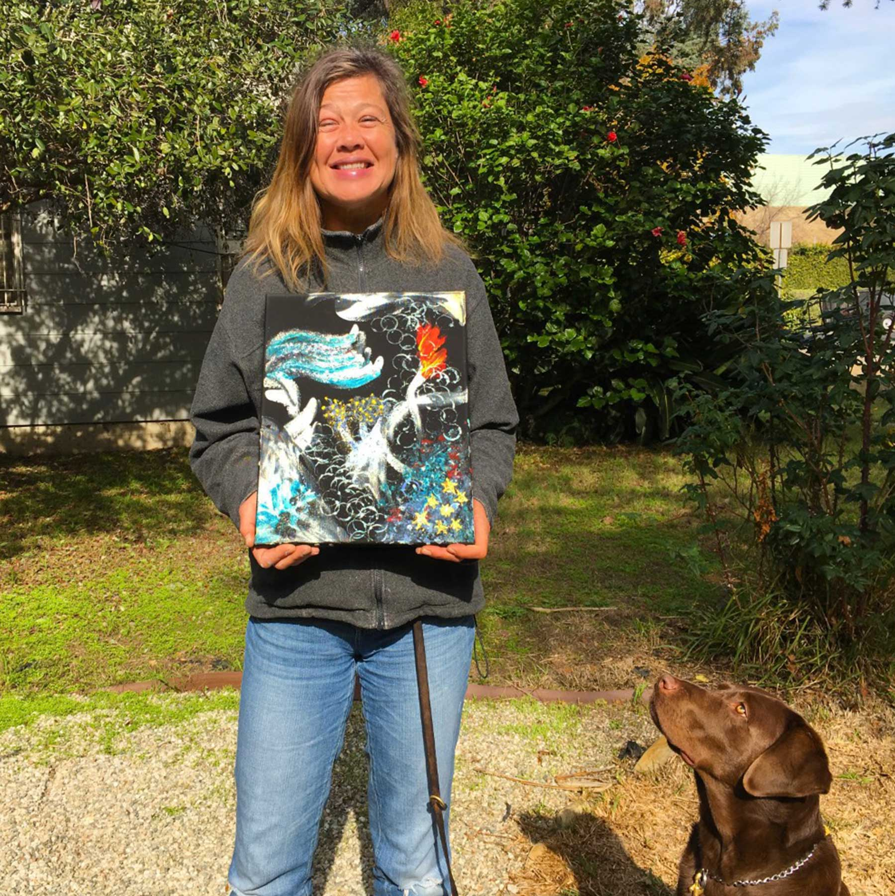 A photo of Laura Meddens holding one of her paintings-Diving Memories as her art critic Nugget - her faithful guide dog - looks it over.