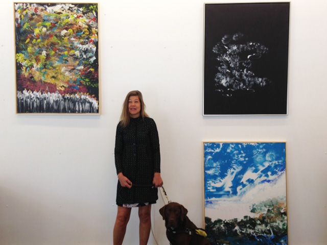 Photo shows Laura Meddens and her Seeing Eye® guide dog 'Nugget' standing between three of her paintings at an exhibition in Amsterdam.