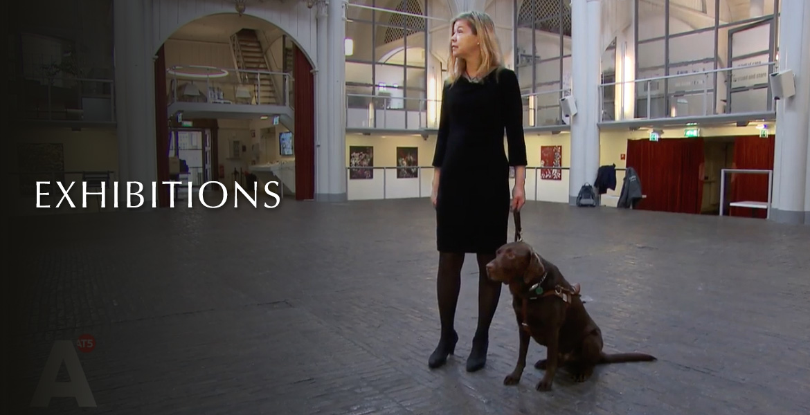 Exhibitions. Image: Photo of painter Laura Meddens standing with her Seeing Eye Guide Dog Nugget in the middle of the historic Amstelkerk in Amsterdam during her exhibition there.