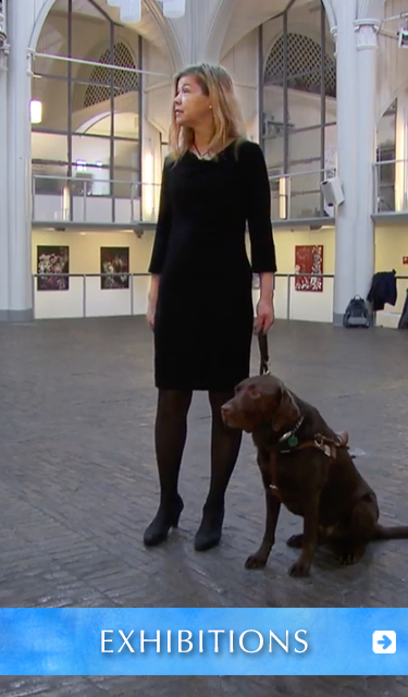Exhibitions. Image: Photo of painter Laura Meddens standing with her Seeing Eye guide dog Nugget in the center of her exhibition at the historic Amstelkerk in Amsterdam.