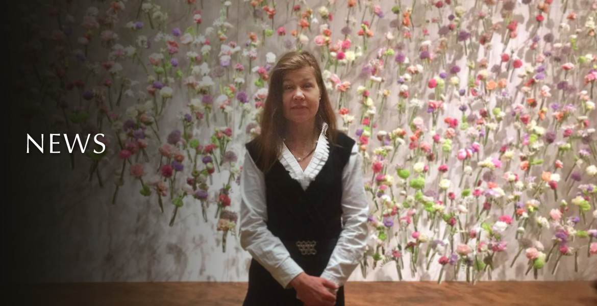 News. Image: Photo of Laura Meddens taken against a backdrop of flowers at TEFAF - The European Fine Art Fair.