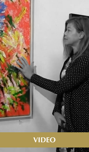 "Video. Image: Video frame of Laura reaching out and touching her painting ""Tropical Splash"" ."